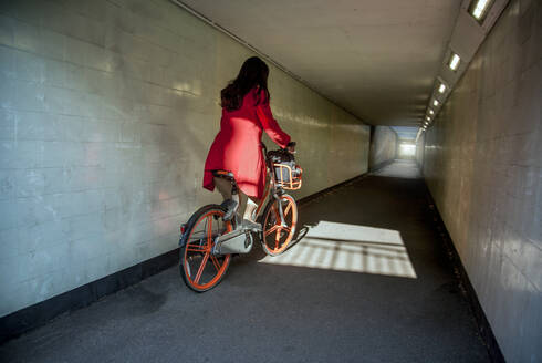 Young woman riding through an underpass on a rental bike - AJOF00093