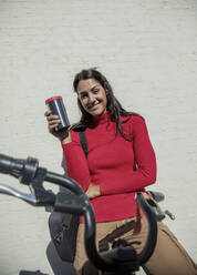 Young woman with bicycle, leaning on wall, drinking coffee from reusable cup - AJOF00105