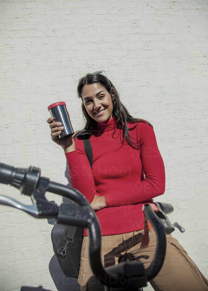 Young woman with bicycle, leaning on wall, drinking coffee from reusable cup - AJOF00105 - LOUIS CHRISTIAN/Westend61
