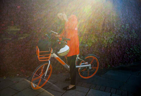 Young woman activating rental bike with smartphone app - AJOF00108