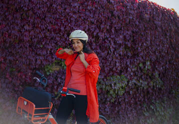 Young woman sitting on bicycle, putting on saftey helmet - AJOF00111