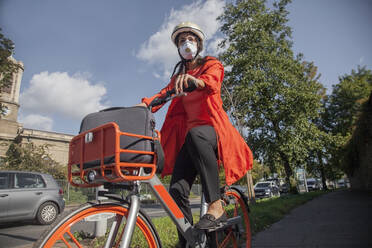 Young woman with helmet and face mask, riding bicycle in the city - AJOF00114