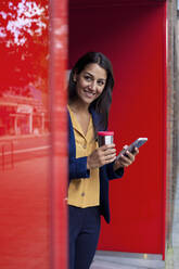 Young businesswoman with reusable coffee cup and smartphone , leaning on wall - AJOF00120