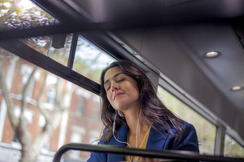 Young woman listening music on a bus with earphones, eyes closed - AJOF00123