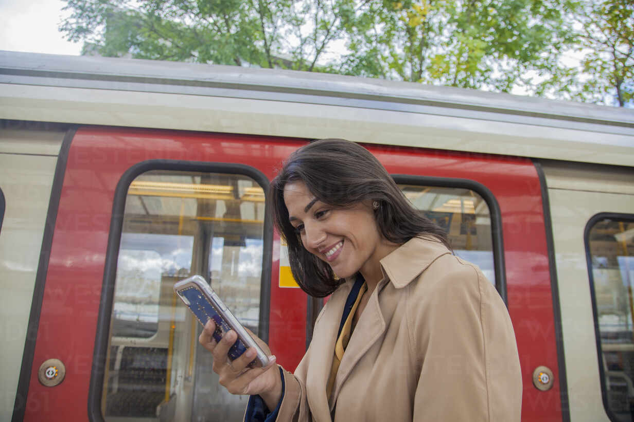 Young businesswoman using smartphone infront of commuter train - AJOF00126 - LOUIS CHRISTIAN/Westend61