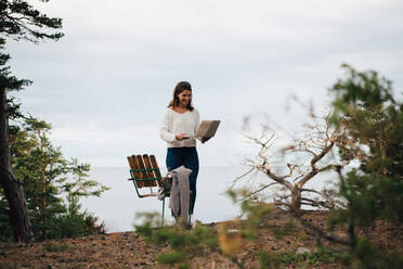 Smiling young woman with laptop standing by chair in forest against sky - MASF16134