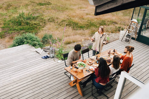 High angle view of woman talking with friends while enjoying dinner in patio - MASF16146
