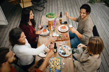 High angle view of friends enjoying drinks while having food during garden party - MASF16149