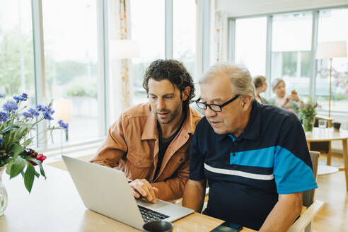 Man assisting grandfather using laptop at dining table in retirement home - MASF16221