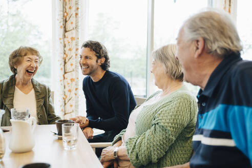 Smiling man visiting his grandmother and her friends at retirement home - MASF16239