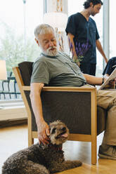Retired senior man sitting with newspaper on armchair while stroking dog by friends and caretaker at elderly nursing hom - MASF16257