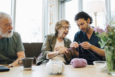 Retired senior woman teaching knitting to male nurse while sitting on sofa at elderly care home - MASF16269