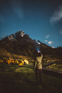 Traveler looking at starry sky in mountains - CAVF72703