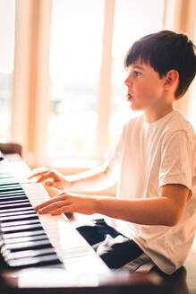 Young boy focused while playing the piano in a sunny room. - CAVF72811