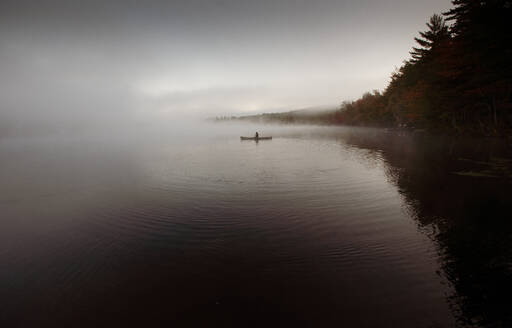 Solo paddling on a misty pond at sunrise. - CAVF72853