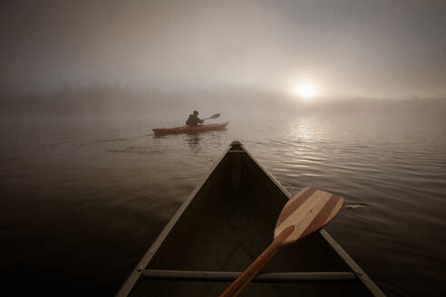 Solo paddling on a misty pond at sunrise. - CAVF72856