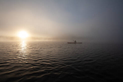 Solo paddling on a misty pond at sunrise. - CAVF72862