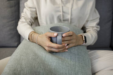 Crop view of woman relaxing with cup of tea on the couch at home - KMKF01180