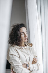Portrait of pensive woman looking out of window - KMKF01192