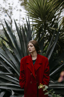 Woman with red coat in a park - TCEF00002