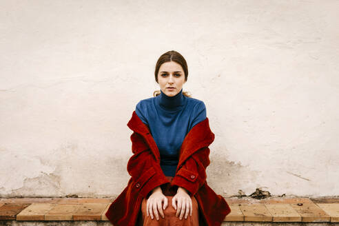 Close up portrait of woman with blue turtleneck pullover and red coat sitting on a step - TCEF00008