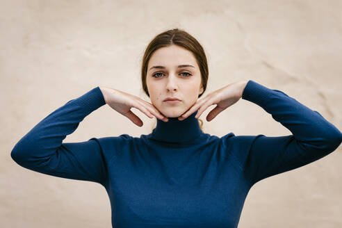 Close up portrait of woman with blue turtleneck pullover, hands on chin - TCEF00014