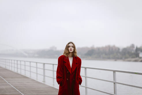 Portrait of young woman wearing red coat on a bridge during rainy day - TCEF00026