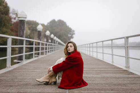 Portrait of young woman wearing red coat, leaning on railing on rainy day - TCEF00029