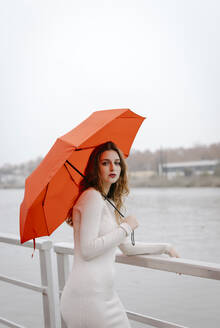 Portrait of young woman with red umbrella, leaning on railing during rainy day - TCEF00032