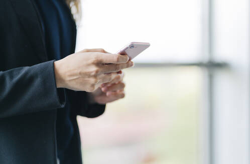 Close-up of businesswoman using cell phone - DGOF00021