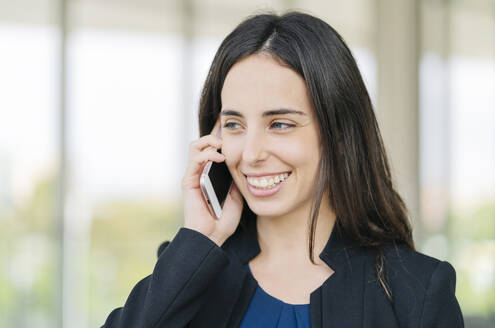 Portrait of happy businesswoman talking on the phone - DGOF00024