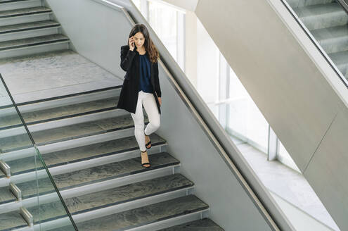 Businesswoman walking down stairs talking on the phone - DGOF00027