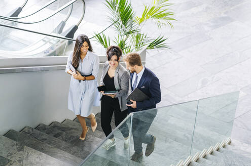 Business team with portable devices walking upstairs - DGOF00030