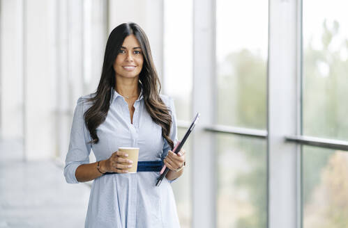 Portrait of smiling businesswoman with tablet and takeaway coffee at the window - DGOF00045