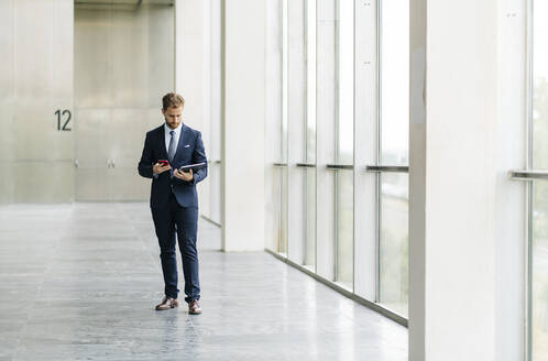 Businesman using tablet and smartphone at the window - DGOF00054