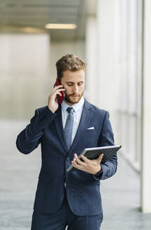 Businessman holding tablet talking on the phone - DGOF00057