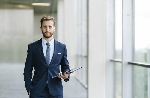 Portrait of confident businessman holding tablet - DGOF00060