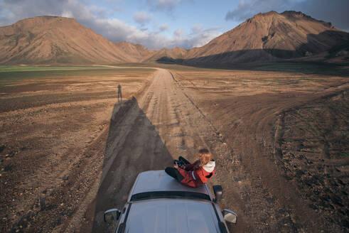 Woman traveller enjoying scenic view on vehicle, Landmannalaugar, Highlands, Iceland - CUF54544