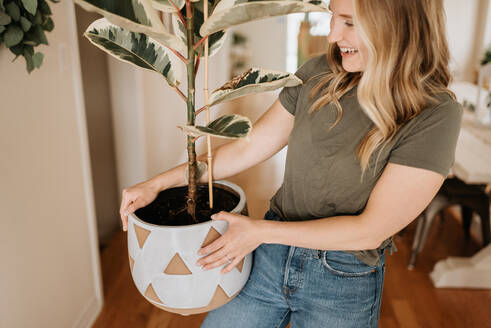 Woman carrying large pot of house plant - ISF23657