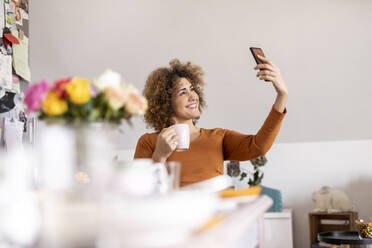 Woman holding coffee cup and taking a selfie at home - FMKF06072