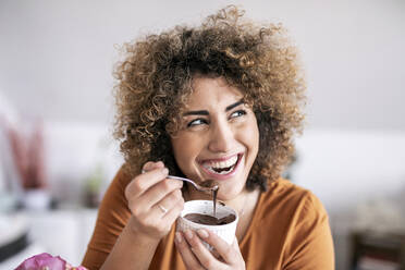 Portrait of happy woman eating chocolate spread at home - FMKF06075