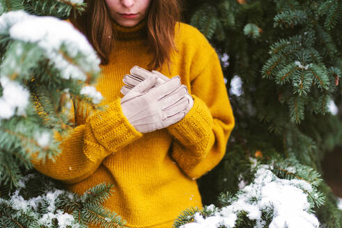 Woman looking away while standing by snow covered trees - CAVF73236