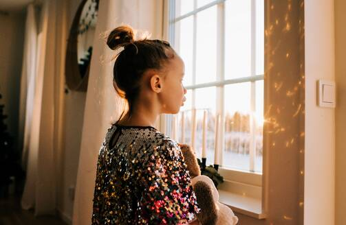 Young girl playing with her toy at home in a sparkly dress at sunset - CAVF73338