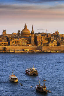 Malta, Valletta, City skyline at sunset, boats in Marsamxett Harbour in foreground - ABOF00455