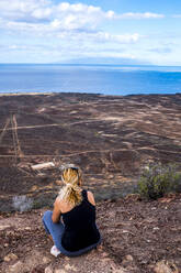 Rear view of woman sitting on viewpoint, Tenerife, Spain - SIPF02118