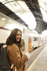 Portrait of smiling young woman with cell phone at the train station - VABF02493