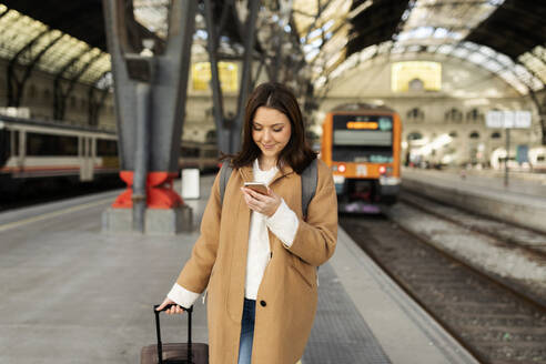 Young woman using cell phone at the train station - VABF02499