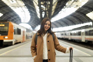 Portrait of smiling young woman at the train station - VABF02514