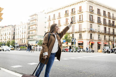 Young woman in the city hailing a taxi, Barcelona, Spain - VABF02517