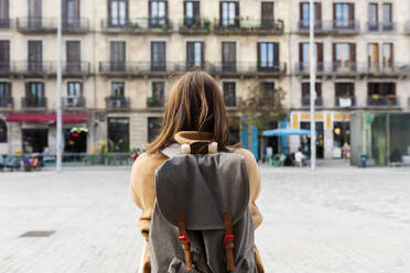 Rear viewof young woman with backpack in the city, Barcelona, Spain - VABF02523